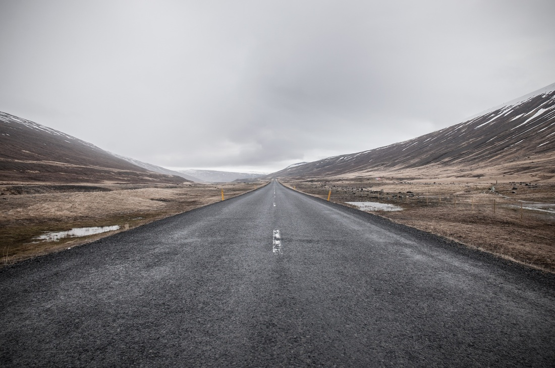 Photo of an empty tarmac road with hills on the side and in the horizon. The weather is cloudy.