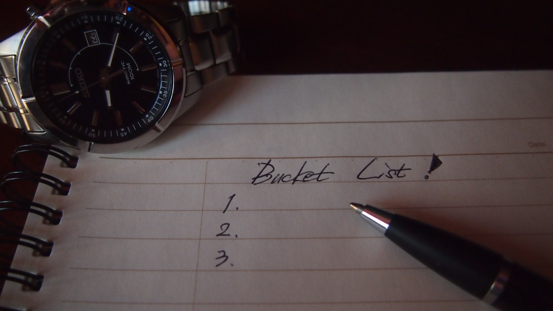A blank note titled bucket list with a pen on the side and a watch next to it.