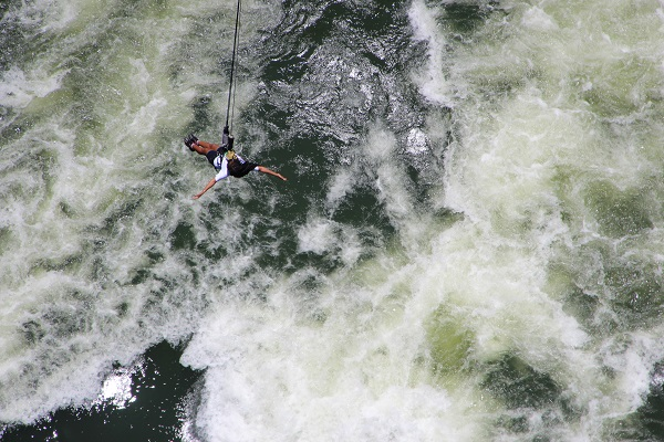 Nelly hanging on a cord during a gorge swing at Victoria Falls with her arms wide open