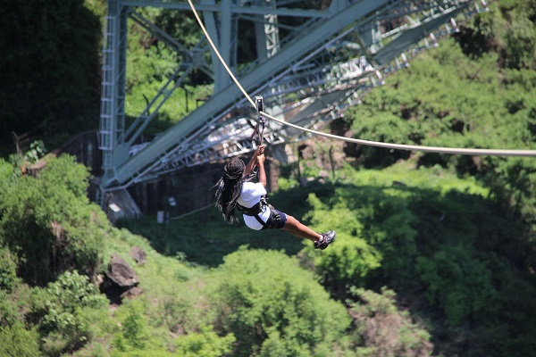 Nelly mid slide on a zipline off the Victoria Falls bridge in Zambia/Zimbabwe border
