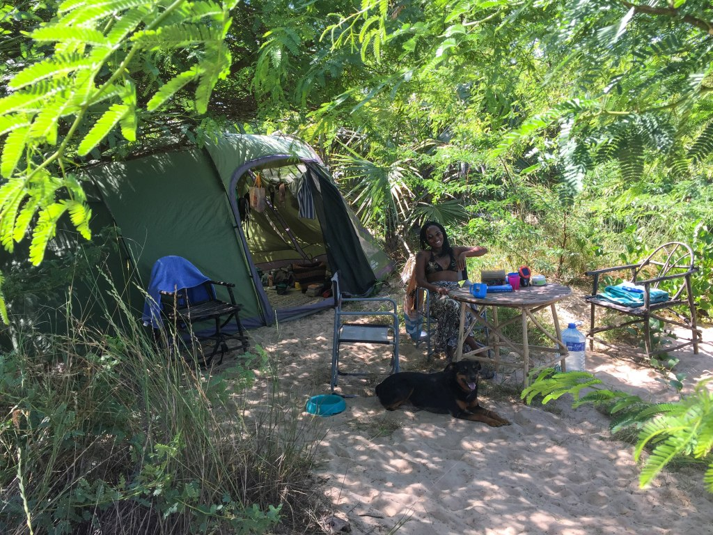 Gustav the dog and Nelly seated facing the camera next to their campsite at Barefoot Beach Camp in Mambrui, Malindi.