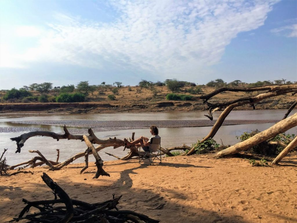 Nick seated on a chair by the banks of the Ewaso Nyiro River reading a book.