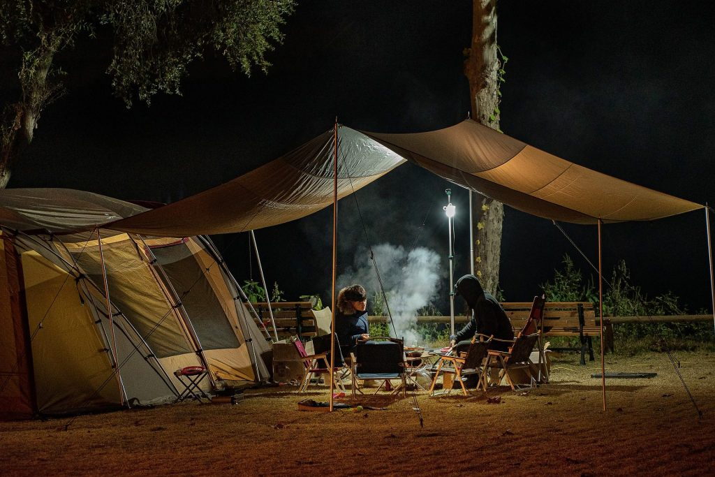 Safety of a camp site: two campers sitting outside their tent at night