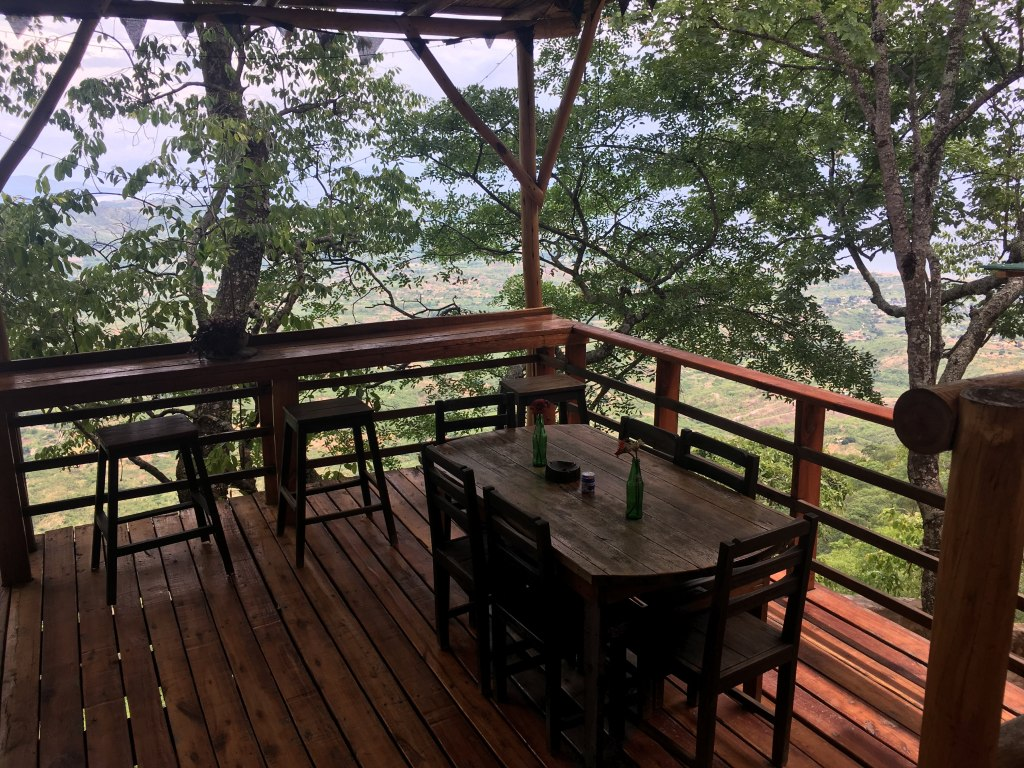 A wooden table and chairs dining area with a view built on a wooden deck at Mushroom Farm - Malawi.