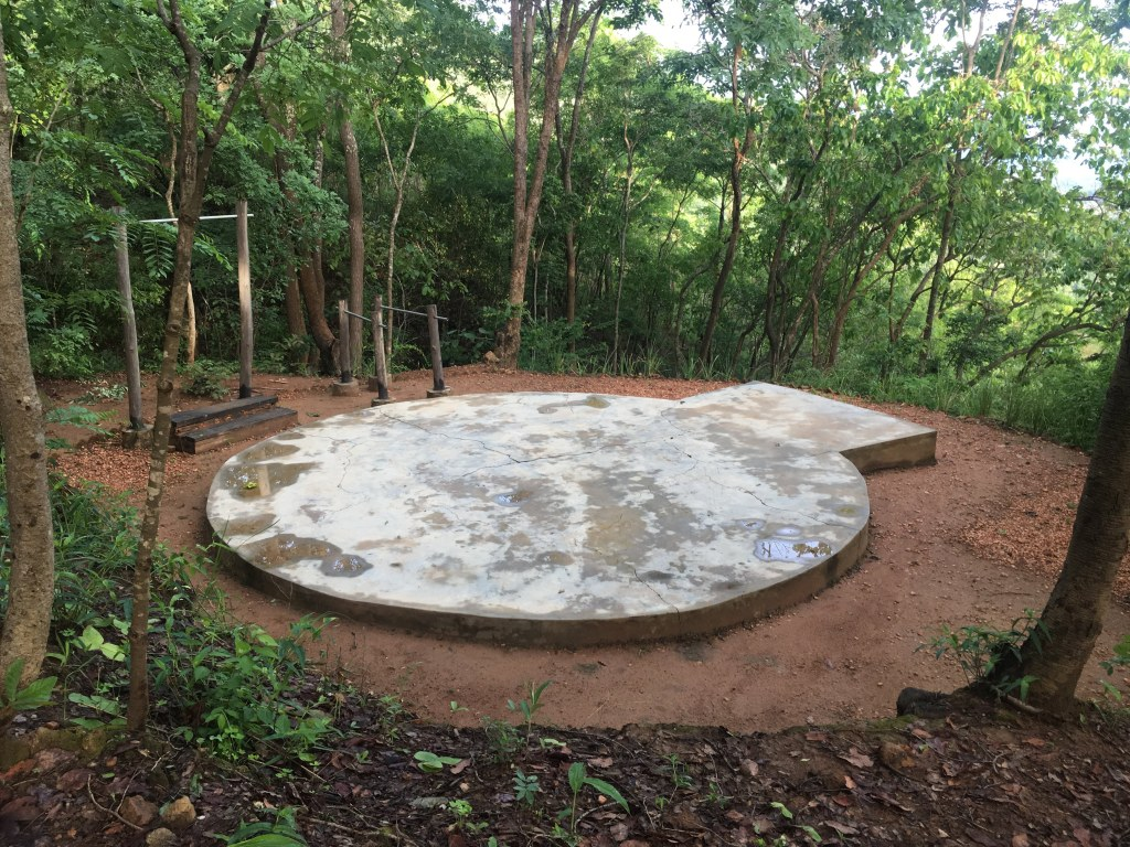 A concrete yoga deck surrounded by trees at the Mushroom Farm, Malawi.